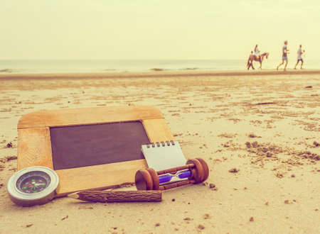 stationery items: journey concept vintage tone image of chalkboard and stationery items For creative idea with blur people riding horse and sea in background.(selective focus on chalkboard) Stock Photo