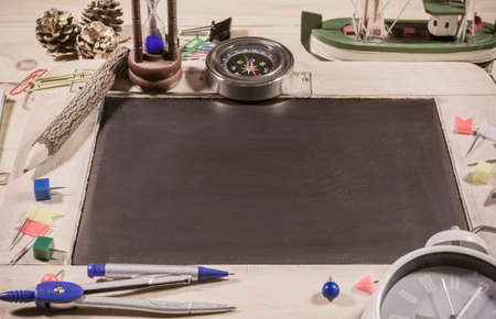 creative artist: vintage tone image of wooden table top view of the chalk board with creative stationery items to draw, paint. For creative idea work of the artist.