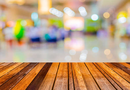 blurred image of wood table and trade show in shopping mall for background usage .