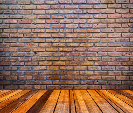 vignetted: wood floor and red brick wall texture grunge background with vignetted corners of image.