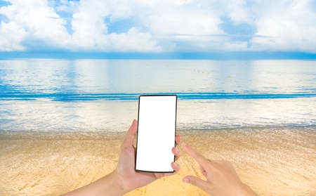 background photo: blur image of sea shore and clear blue sky  and phone  for background usage.