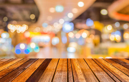 wood trade: blurred image of wood table and trade show in shopping mall for background usage .