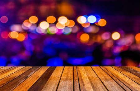 Światła: obraz tabeli drewna i niewyraźne tło bokeh z kolorowych świateł (niewyraźne)