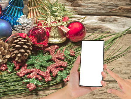 touch screen phone: male hand is holding a modern touch screen phone and Christmas ornament