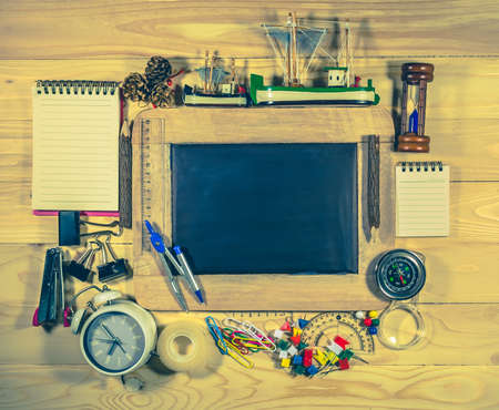 stationery items: wooden table top view of the chalk board with creative stationery items to draw, paint. Stock Photo