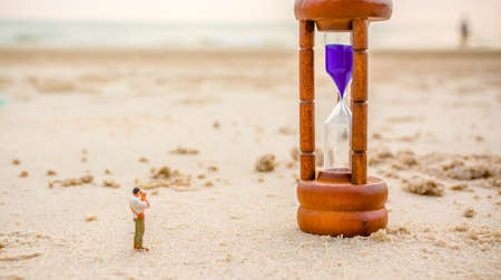 hour glass figure: selective focus on sandglass image of mini figure dolls photographer take picture on sandglass on the beach blur in background.