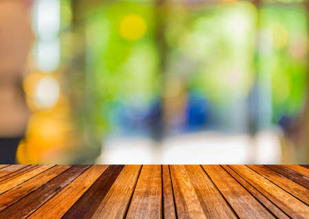 indoor background: Coffee shop blur background with bokeh and brown wood table image.