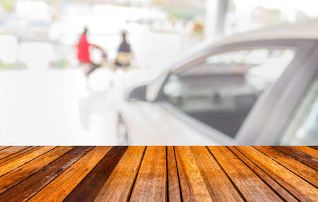 commercially: wood floor and blur image of Commercially cars stand in show room of car shop for background usage.