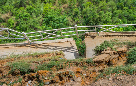 soil erosion: image of white fence fall down by soil erosion with green forest in background.