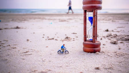 mini bike: vintage tone image of mini figure dolls biker and sandglass on the beach blur in background. Stock Photo