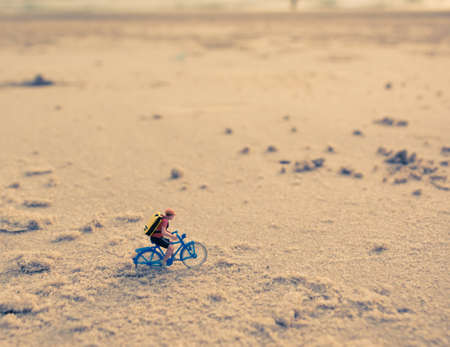 mini bike: image of mini figure dolls biker on the beach blur in background.