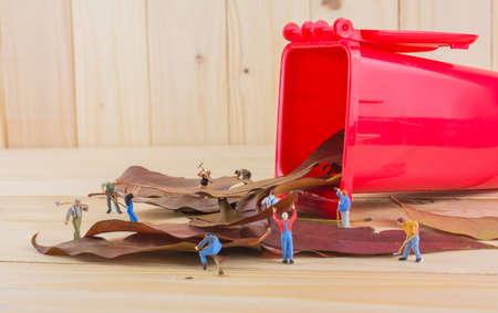 envases plasticos: imagen del concepto de la idea de mini trabajador figura muñecas de recoger las hojas secas en la papelera de reciclaje rojo. (es decir, como grupo de personas que ayudan a mantener el ambiente seguro)