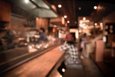 blur image of Abstract blurry sushi counter and customer  in vintage style decoration restaurant.