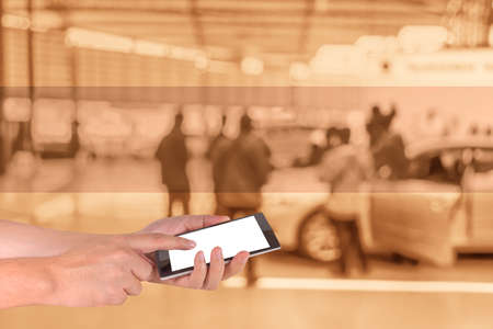 commercially: male hand is holding a modern touch screen phone and blur image of Commercially cars stand .