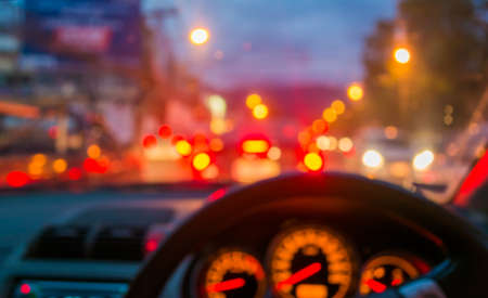 blur image of inside cars with bokeh lights with traffic jam on night time for background usage.