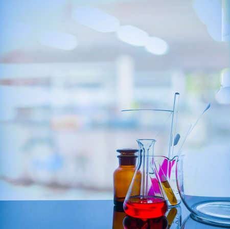 Lab glassware with blur laboratory in background.