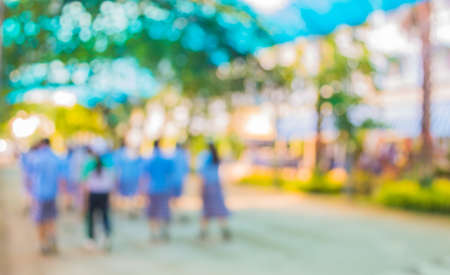 blur image of Long corridor with people in open space to the green garden with bokeh for background usage .