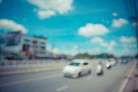 abstract blur of the road with car on day time for background usage. (vintage tone)