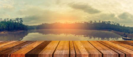 Cais de madeira ou uma antiga mesa de madeira com imagem desfocada de lago e céu azul em segundo plano