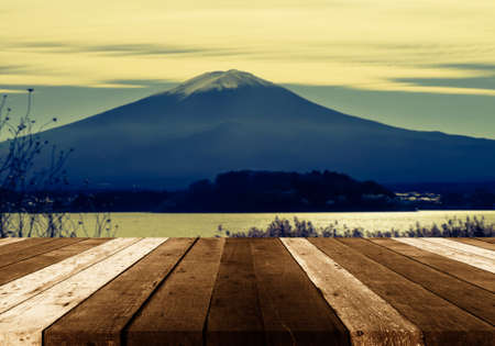 wood table and blur image of fuji mountain in japan for background usage . Stock Photo