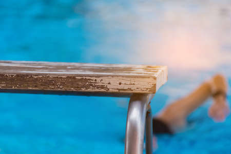 image of platform and blur people in swimming pool.(focus on platform) Stock Photo