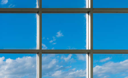 image of old office square windows to see blue sky and white clouds in background.