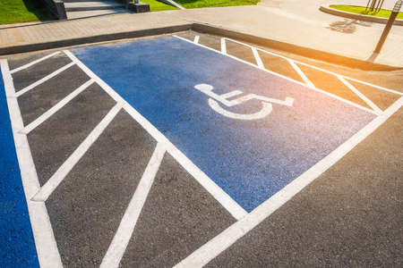 Image of blue new handicapped symbol shows sign reserved for disability person on car parking space. Imagens