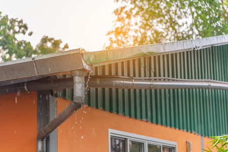 Image of roof gutter pipeline during the raining day with water drainage.