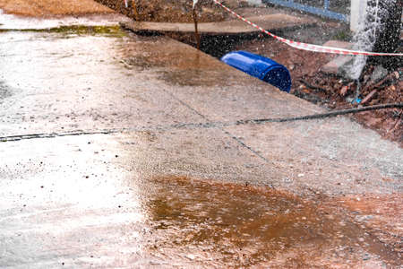 Image of tap water fountain leaking from the pipeline after poor street construction and fix ground basement.