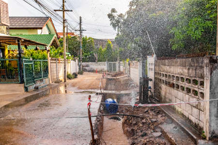 image of tap water fountain leaking from pipeline after poor street construction and fix ground basement. Archivio Fotografico
