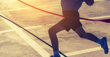 Silhouetafbeelding van lint bij de finishlijn met de winnaar van de kinderen het oversteken. (Focus op lint)