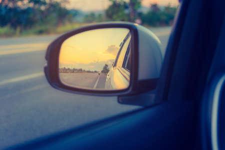 Bild des Auto-Außenspiegels, um die perspektivische Straße hinter der Sonnenuntergangszeit für den Hintergrund zu sehen.