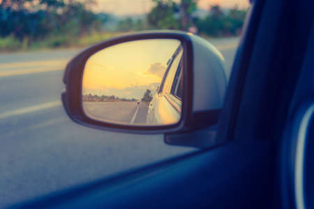 obraz lusterka skrzydło samochodu, aby zobaczyć perspektywę drogi za na zachód słońca na tle.