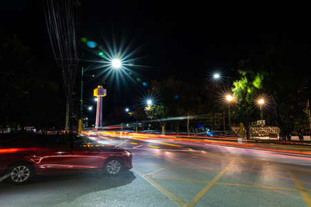 Long exposure image of the landmark building clock tower in Chiangmai university,Thailand is the largest traffic roundabout circle in center area on night time.