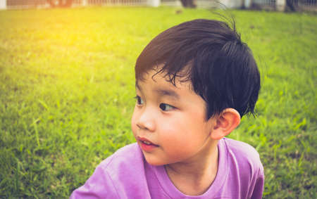 image of Young Asian boy looking on left side in park with green grass field in background.