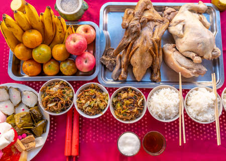 Food on the table for gods worshiping Chinese beliefs, consisting of chicken, duck, fried rice, rice, tea, fruit, various desserts in the China New Year. Banque d'images