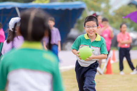 A smiling grumpy boy runs in the lawn during the competition, holding a green ballon ball in his school sports uniform.