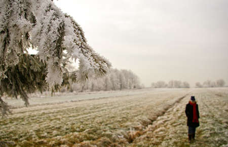 Lonely girl standing in the middle of the frost covered field. Some icy branches on the left side Stock Photo - 2671944