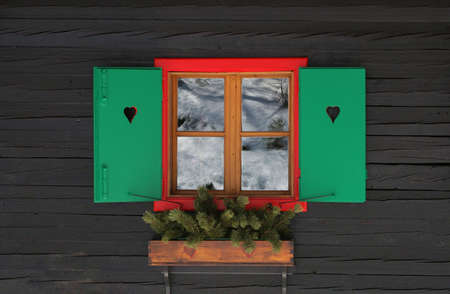 visible: Colorful window frame with shutters. Snow reflection is visible Stock Photo