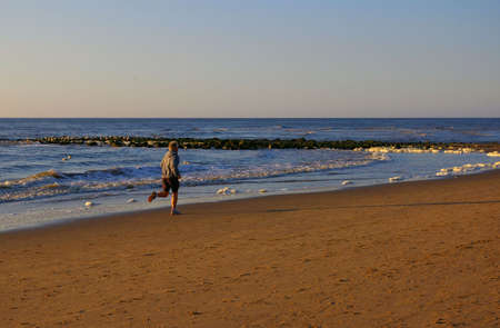 Young man jogging on the beach during sunset. Stock Photo - 3105145