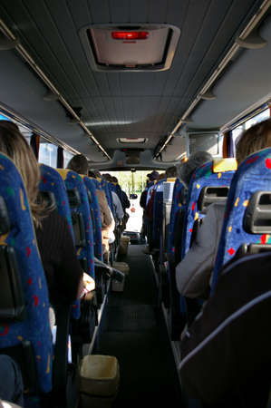 Picture of the inside of a bus with passenger sitting in the seats Stock Photo