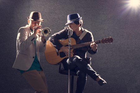 Two musicians playing guitar and singing