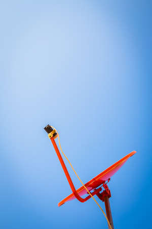 parabolic mirror: orange satellite dish on blue sky Stock Photo