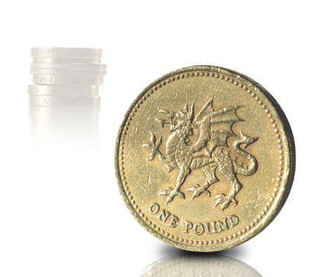 Macro of UK pound coin with stacked coins in the background against a white background. Copy space. photo