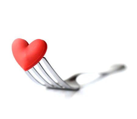 Macro studio image of stainless steel fork with red heart. Concept image for Valentine dinnerlove foodlove cooking etc. Differential focus with shallow DOF. Copy space. Stock Photo