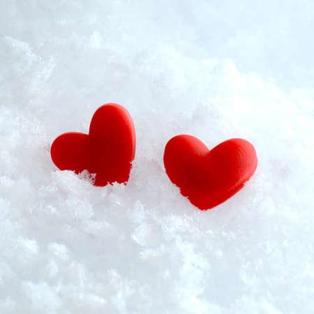 enero: Estudio macro de dos corazones rojos que mienten en la nieve. Copiar el espacio.