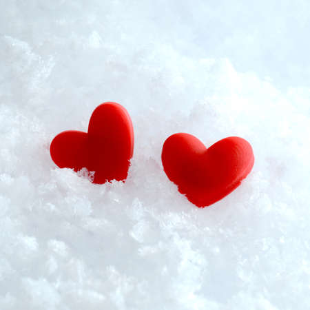 new love: Studio macro of two red hearts lying in the snow. Copy space.