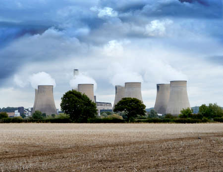Environmentally non-friendly coal-fired power station in the East Midlands of the UK viewed from a rural perspective with dramatic overhead skies. Copy space.
