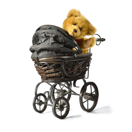 Soft fluffy teddy bear looking back and waving while sitting in a vintage style pram/stroller. Copy space. DESIGN IDEA! Potential of adding a flag or message card in raised paw. Standard-Bild