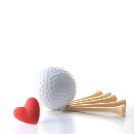 Isolated white golf ball with wooden tees on white with red heart. Concept Father's Day theme
